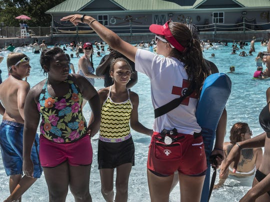 Lifeguard Alyssa Seligmann, center, who attends Mt. Juliet High School, directs people at the pool at Nashville Shores. This will be her last weekend working before she goes back to school.
