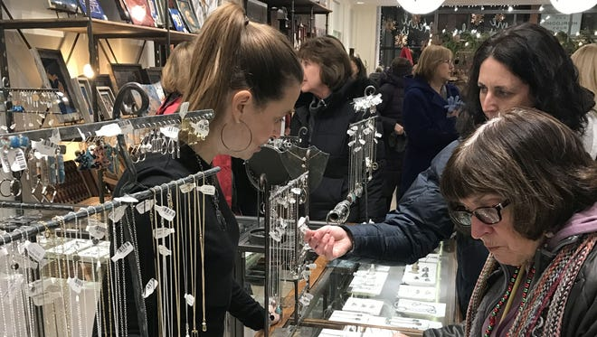 Shoppers examine the jewelry selections at The Artisan's Bench in Brighton during a Ladies Night Out shopping event on Dec. 6, 2018. The next event is Thursday.