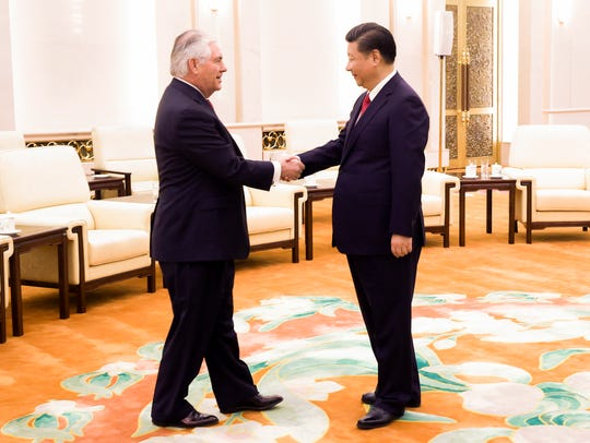 China's President Xi Jinping, right, shakes hands with