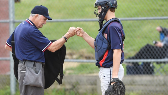 Umpire Ron Davis gets a bump from Morgan catcher Clayton Cook before the start of the Raiders' game against John Glenn recently. Davis is retiring this year after 50 years behind the plate.