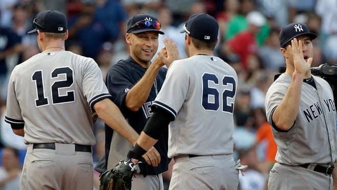 New York Yankees' Derek Jeter, center, celebrates his team's 9-5 win over the Boston Red Sox with Austin Romine (62) and other teammates after the last baseball game of Jeter's  career Sunday, Sept. 28, 2014, at Fenway Park in Boston.