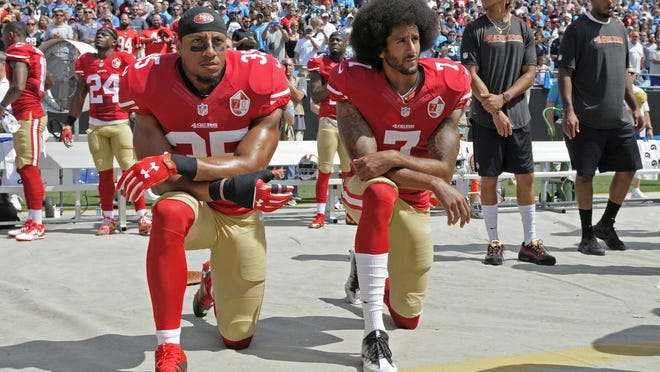 Colin Kaepernick (7) and Eric Reid (35) of the San Francisco 49ers kneel during the national anthem before a game against the Carolina Panthers in Charlotte, N.C., in September 2016. Four years after Kaepernick spoke out against racism and eventually lost his job for peacefully protesting, the NFL said it supports his fight and now encourages players to stand up for racial equality and social justice.