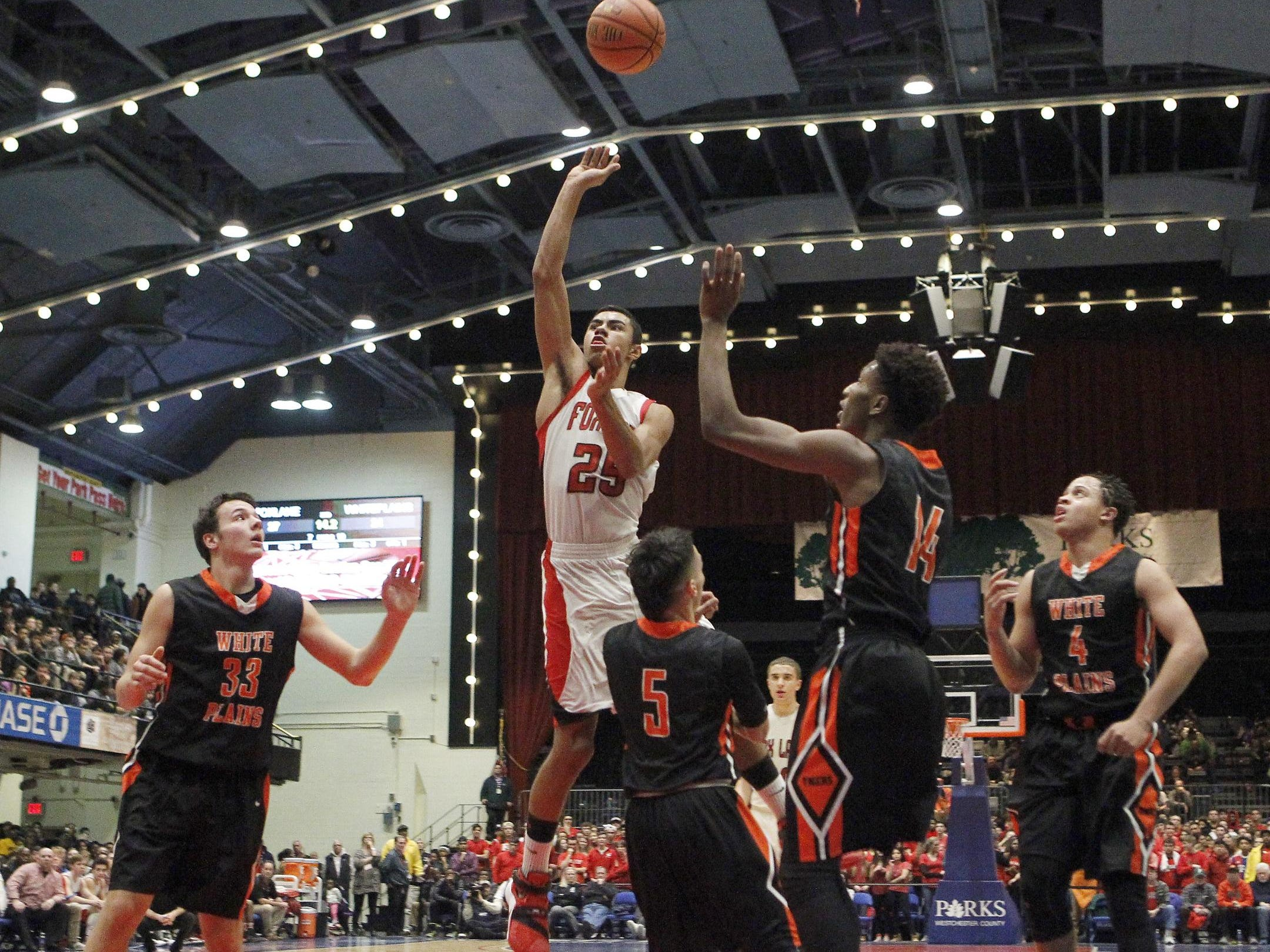 Fox Lane's Alex Olsen drives past White Plains' Luis Cartagena during a Class AA semifinal at the County Center in White Plains on Friday.