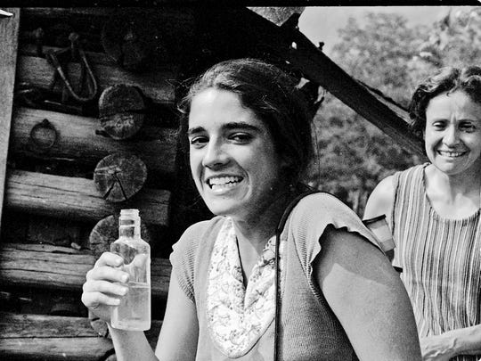 This photo by Caroline Kennedy from 1973 shows her friend Allyson Riclitis trying moonshine as Marie Cirillo, right, looks on while visiting Jim Huddleston's home near Eagan, Tenn.