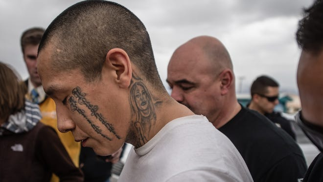 In this March 12, 2016 photo, escaped inmate Lionel Clah is escorted into the State Police office in Albuquerque after being captured. The New Mexico Corrections Department plans to fire two guards who were in charge of a transport van when Clah and another violent felon escaped, a corrections union representative said Friday, April 1.