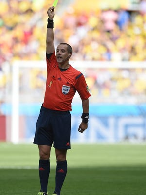 U.S. referee Mark Geiger, Beachwood, shows a yellow card during a Group C match between Colombia and Greece.
