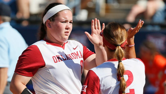 Oklahoma pitcher Paige Parker, left, high-fives Sydney Romero (2) at the end of an inning during the championship game of the Big 12 college softball tournament at ASA Hall of Fame Stadium in Oklahoma City, Saturday, May 13, 2017. Oklahoma defeated Oklahoma State 2-0. (Nate Billings/The Oklahoman via AP)