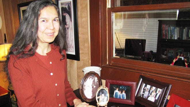 The walls, desk, office and fireplace in the Elmira home of Reyna Sandoval are filled with photos of family and artwork of her native Mexico.