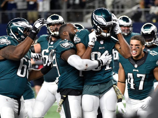 Philadelphia Eagles' Jordan Matthews, right front, is congratulated by teammates after scoring a touchdown on a pass play in overtime of an NFL football game against the Dallas Cowboys on Sunday, Nov. 8, 2015, in Arlington, Texas. The Eagles won 33-27.