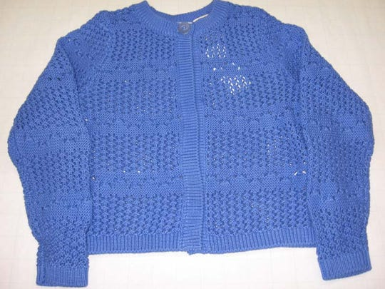 A spare button attached to the label of Fisherman's and Open Stitch Children's Sweaters could pose a choking hazard.