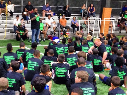 Edison Jacquez motivates a group of youngsters during a speaking engagement at a local football camp.