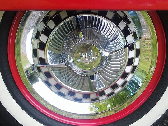 The hand-pointed checkerboard hubcaps with ruby red inset on valve stem of Jim Goulette's 1955 Oldsmobile 88.