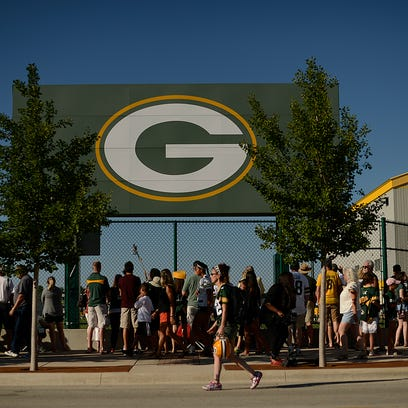 Fans watch along the fence line during the Green Bay