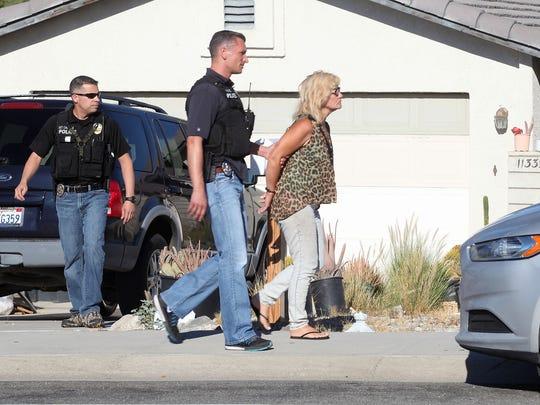 Police take Marie Mifflin into custody during police raids in Desert Hot Springs on June 16, 2016.