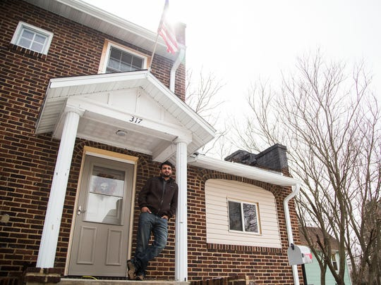 "Zalmay ""Zee"" Niazy stands on the front step of his home in Iowa Falls on Thursday, April 5, 2018. Niazy came to the United States seeking political asylum after serving as a translator for the US Army in his native county of Afghanistan. While waiting almost a year to hear if he will be granted US citizenship he's purchased and remodeled his home and has continued to build a successful handy man business in Iowa Falls."