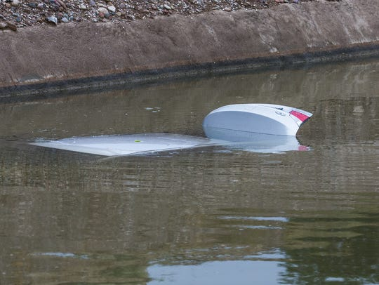 A car remains submerged in a canal at Alma School Road
