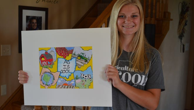 "Regan Draeger holds her winning painting from the 2013 ""Agriculture is Cool"" contest hosted by Governor Kasich. This year, Draeger  won the contest for the third time with a mixed media painting."