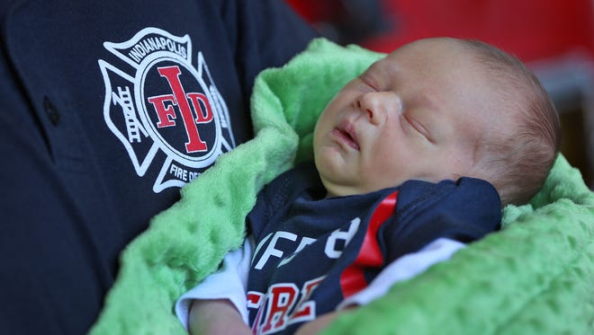 An Indianapolis Fire Department firefighter holds a sleeping Dylenn VanDuyn, as they reunite at IFD Station No. 8, Saturday, Oct. 10, 2015.  Dylenn was delivered outside the fire station on Sept. 28, 2015, when his parents realized they wouldn't make it to the hospital.