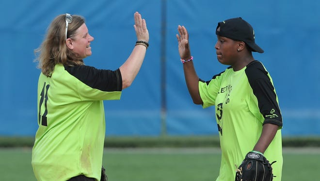 Olympic gold medalist and Special Olympics coach Dionna Harris (left) shares a high-five with Ka'Neisha Mickens of the team of students from Networks School for Employability Skills during the Special Olympics softball competition at the University of Delaware Saturday.