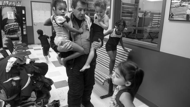 Bob Gibbons tries to get six of his seven children ready for gymnastics class at Star Bound Gymnastics in Bridgeton earlier this year. Photographer Denise Henhoeffer spent extra time with the family to get to know them and allow the children to become relaxed when she was shooting.