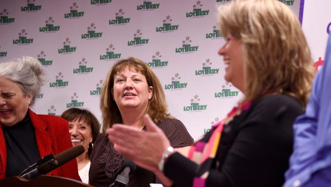 Amy O'Neal, center, of North American Stamping Group in Portland, Tenn., will share the winning $420 million Powerball prize with 19 co-workers. The group was introduced in Nashville on Tuesday, Nov. 29, 2016, as the winners of the Saturday, Nov. 26, 2016, drawing.