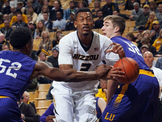 Missouri's Johnathan Williams III, center, is fouled by Lipscomb's Malcolm Smith, left, as he tries to squeeze by Brett Wishon, right, during the first half of an NCAA college basketball game Saturday, Jan. 3, 2015, in Columbia, Mo. (AP Photo/L.G. Patterson)