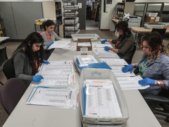 Election workers hand verify mail-in-ballots that vote