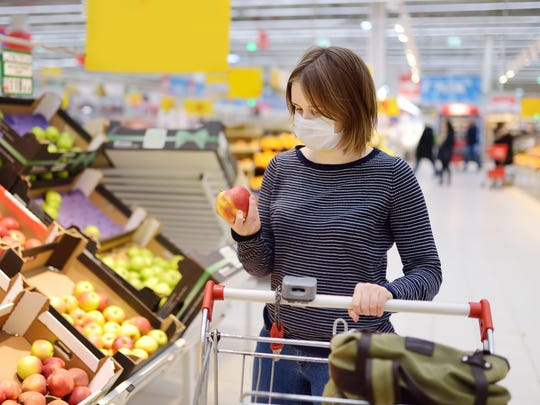 Woman wearing a surgical mask as she shops in a grocery store.