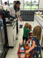 Young shoppers go through the check out at the Fareway store in Johnston.