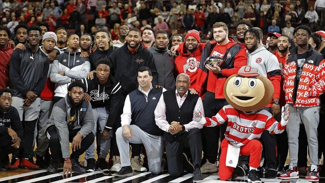 Ohio State Football poses for a football with Brutus Buckeye at halftime of the Ohio State and Minnesota game at Value City Arena in Columbus, Ohio on January 23, 2020.