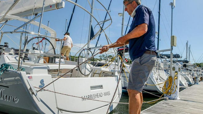 Narragansett Sailing School & Charter owner Rich Munson secures clients' boats along the dock at Safe Harbor Cove Haven in Barrington. [The Providence Journal / David DelPoio]Original Caption: Narragansett Sailing School & Charter owner, Rich Munson secures and fastens down a client 's boats along the dock at Safe Harbor Cove Haven in Barrington.
