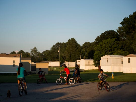 Neighborhood children ride their bikes in White Pine, Tenn., July 3, 2018. Among them are Sherlyn Liberado, 11, (far left) and her brother, Abdiel, 5 (far right). Their father Alberto was detained by U.S. Immigration and Customs Enforcement agents when they raided the Southeastern Provision meat-packing plant where he worked outside Bean Station in April.