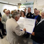 Charlie Switzer signs a ceremonial check for $1 million next to his brothers Bobby, left, and John on Friday at Pensacola State College for a 7,000-square-foot addition to the Anna Lamar Switzer Center including a multiuse space for educational instruction, public lectures and publicly displayed artworks. The expanded art center with be renamed the Charles W. Lamar Studio at PSC's Anna Lamar Switzer Center for Visual Arts.