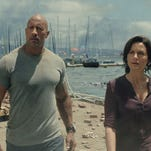 """This photo provided by Warner Bros. Pictures shows Paul Giamatti as Lawrence and Archie Panjabi as Serena, in a scene from the action thriller, """"San Andreas."""" The movie releases in theaters on May 29, 2015."""