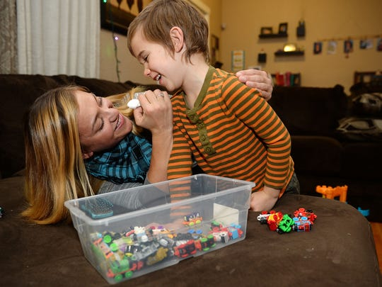 Tara Krook laughs with her son Cash Holtorf, 5, while trying to wipe his face on Tuesday, Dec. 13, 2016, at their Fort Collins home.