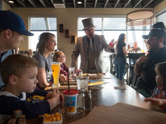 A party watches a magic trick from Peter Donello at D.C. Oakes Brewhouse and Eatery on Tuesday, May 1, 2018.