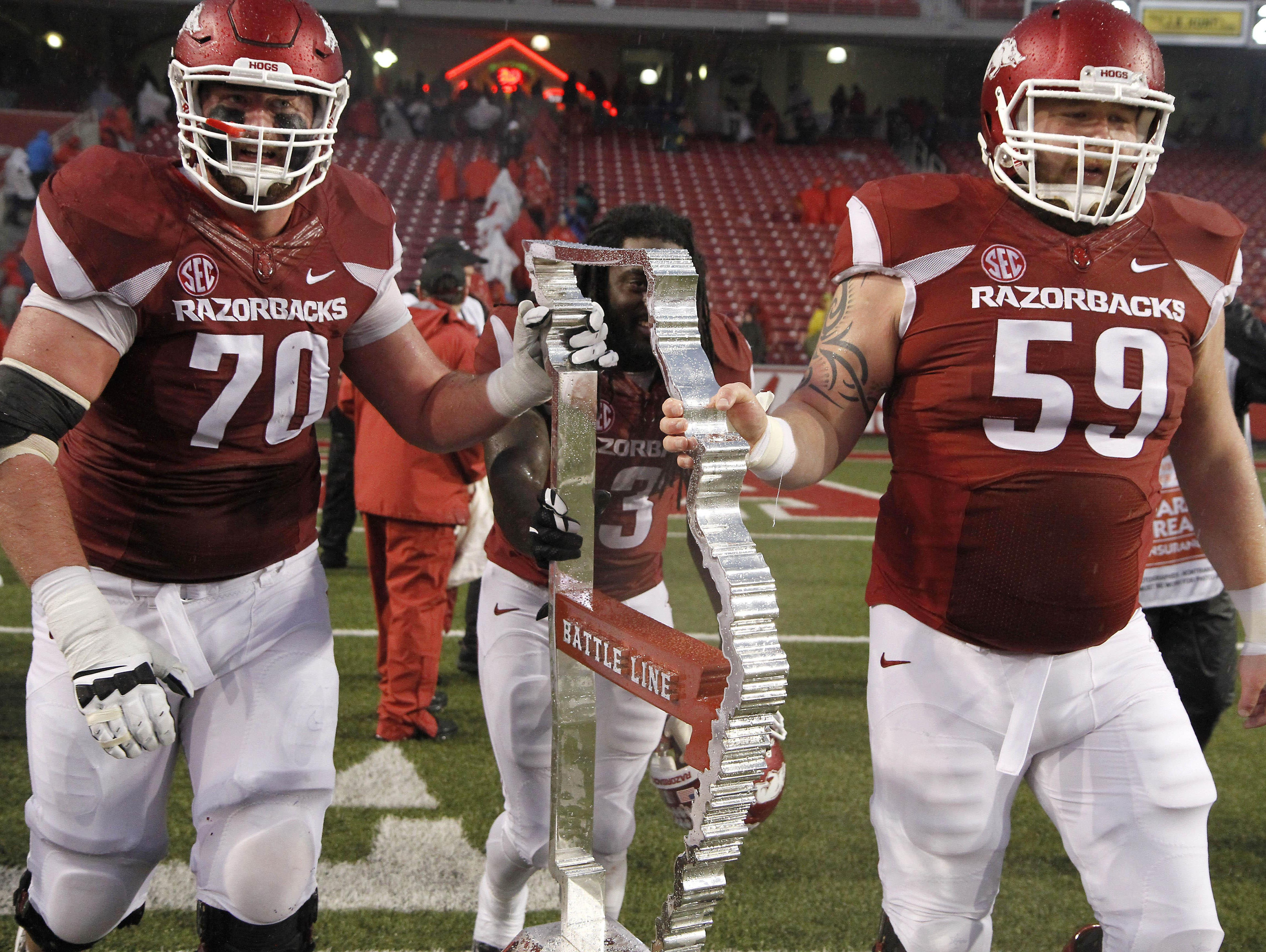 Arkansas' Dan Skipper (70), Alex Collins (3) and Marcus Danenhauer (59) push the Battle Line trophy off the field after a recent game against Missouri in Fayetteville.