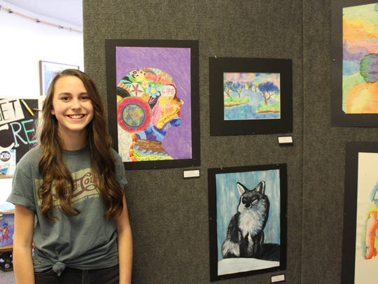 Kaylee Stremcha stands with her self portrait she created