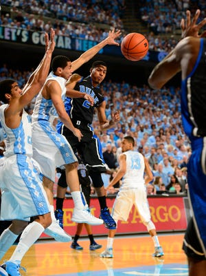Duke Blue Devils guard Quinn Cook (2) passes the ball as North Carolina Tar Heels forward James Michael McAdoo (43) and guard Marcus Paige (5) defend in the first half at Dean E. Smith Center.