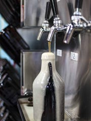 A growler fills with mango IPA at the Growler Garage in South Burlington on Friday, October 16, 2015.
