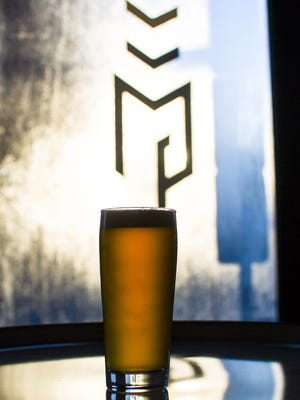 A pint of The Table is seen with the Good Measure Brewing Company logo on the front window of the brewery in Northfield on Monday, December 19, 2016. The company is among those scheduled to take part in the first Winter Brewfest Feb. 11 in South Burlington.