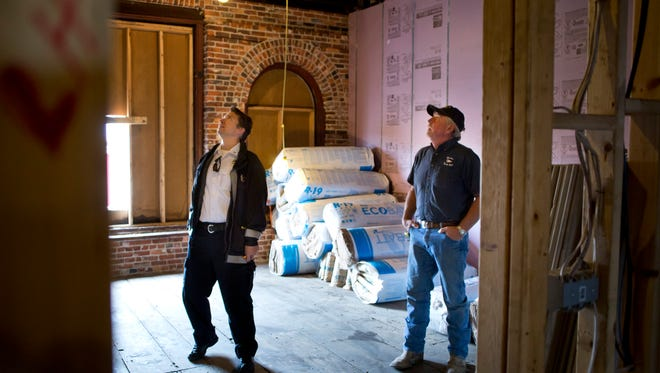 Port Huron Fire Captain Corey Nicholson looks over joists with building owner Larry Jones Tuesday, October 13, 2015 at 230 Huron Avenue in downtown Port Huron. The project to bring 8 loft units and ground floor retail space is scheduled to be completed by January.