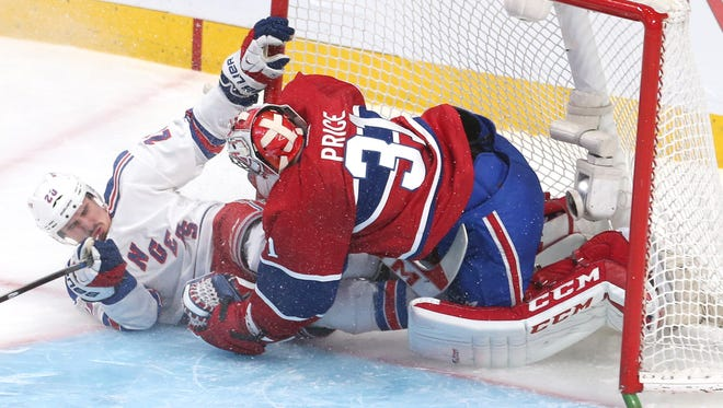 New York Rangers left wing Chris Kreider (20) crashes into Montreal Canadiens goalie Carey Price (31) during the second period in game one of the Eastern Conference Finals of the 2014 Stanley Cup Playoffs at Bell Centre.
