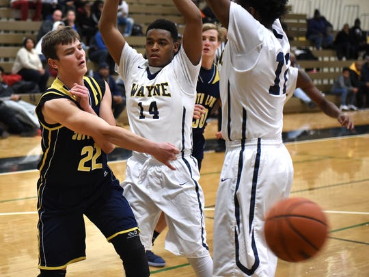 South Lyon's David Szwala (left) tries to split the double-team by Wayne defenders Xavier Moore (middle) and Bryant Napier (right).