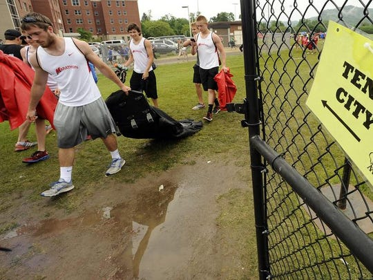 Members of the Marathon track team gather their items and leave the stadium after more severe weather was expected to hit the UW-La Crosse stadium during the 2014 WIAA state track and field meet.
