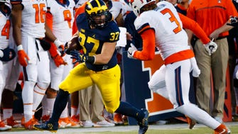 Michigan's Bobby Henderson carries the ball in the second half against  Illinois.