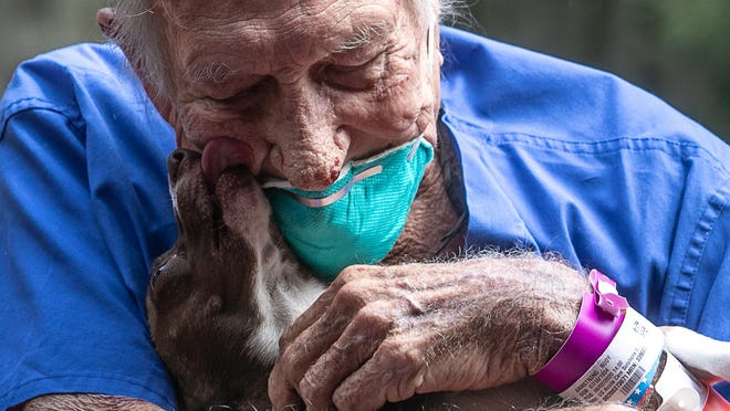 Stroke patient Rudy Armstrong embraces Bubu, his chihuahua mix, who saved his life.