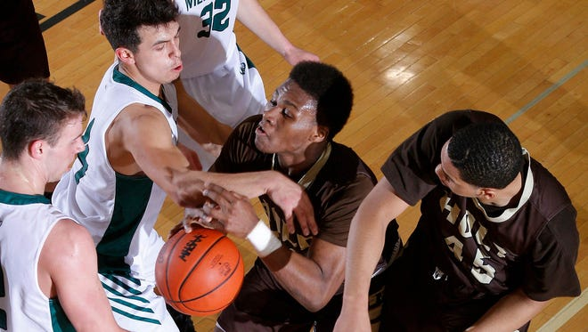 Holt's Ar'tavious King, center, and Myles Baker, right, and Williamston's Sy Barnett, left, and Frankie Toomey battle for the ball Tuesday, Feb. 28, 2017, in Williamston, Mich. Holt won 69-52.
