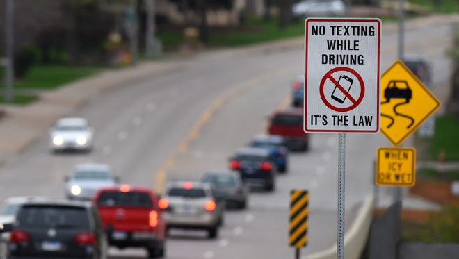 A road sign near Spencer Park along Cliff Avenue reminders drivers that texting while driving is against the law.