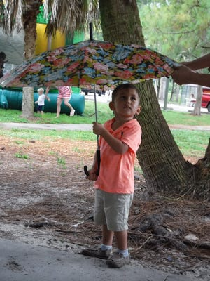 A festivalgoer stays dry under mom's umbrella at the Naples Nites Lions Club event.